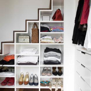 Exemple d'un placard dressing tendance de taille moyenne pour une femme avec un placard sans porte, des portes de placard blanches et un sol en bois brun.