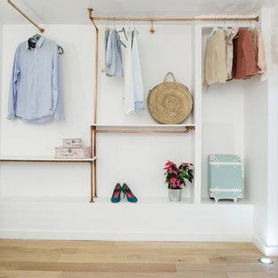 Inspiration for a large scandinavian women's walk-in wardrobe in Paris with light hardwood floors, open cabinets and beige floor.