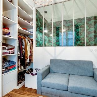 Immagine di un piccolo armadio o armadio a muro per donna nordico con ante bianche, ante lisce e pavimento in legno massello medio