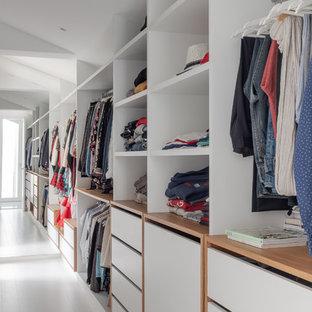 Diseño de armario y vestidor unisex, contemporáneo, grande, con puertas de armario blancas, suelo de madera clara y suelo blanco