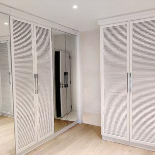 Foto di un grande spazio per vestirsi unisex design con ante a persiana, ante bianche, parquet chiaro e pavimento beige