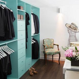 Diseño de vestidor de mujer, actual, grande, con armarios abiertos, puertas de armario azules y suelo de madera oscura