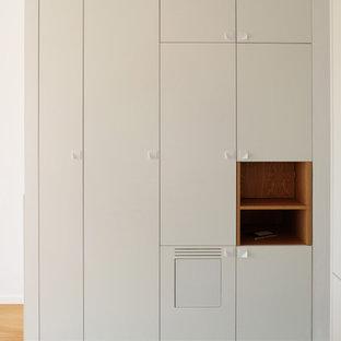 Cette photo montre un petit placard dressing tendance neutre avec un placard à porte plane, des portes de placard blanches et un sol turquoise.