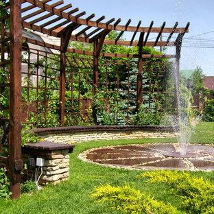 На фото: дворик в средиземноморском стиле с фонтаном и перголой с