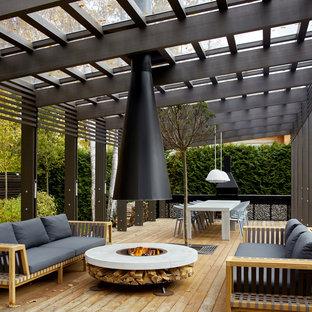 На фото: пергола во дворе частного дома в современном стиле с настилом и уличным камином с