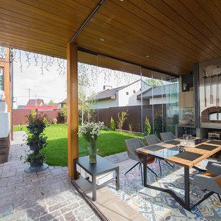 Пример оригинального дизайна интерьера: большой дворик на заднем дворе в современном стиле с летней кухней