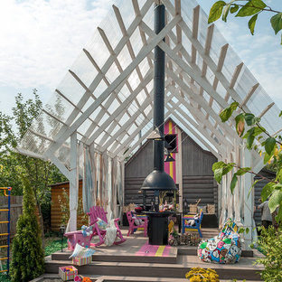 Immagine di un patio o portico boho chic dietro casa con una pergola e un caminetto