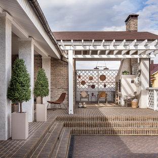 На фото: дворик среднего размера на заднем дворе в средиземноморском стиле с летней кухней, перголой и дорожками из клинкерной брусчатки с