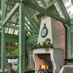 Cette image montre une terrasse traditionnelle de taille moyenne avec des pavés en pierre naturelle, une pergola et une cheminée.