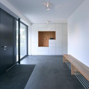 Aménagement d'un grand hall d'entrée scandinave avec un mur blanc, béton au sol, une porte simple, une porte noire et un sol gris.