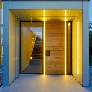 Bild på en funkis ingång och ytterdörr, med en enkeldörr, ljus trädörr, grå väggar och betonggolv