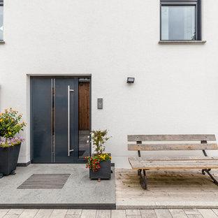 Mittelgroße Moderne Haustür mit weißer Wandfarbe, Betonboden, Einzeltür, schwarzer Tür und grauem Boden in Sonstige