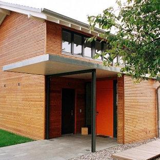 Esempio di un'ampia porta d'ingresso contemporanea con pareti marroni, una porta singola e una porta arancione