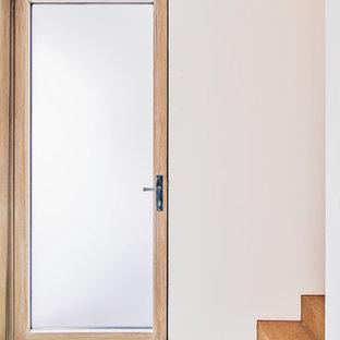 Diseño de puerta principal minimalista con paredes blancas, puerta simple, puerta de madera clara y suelo turquesa