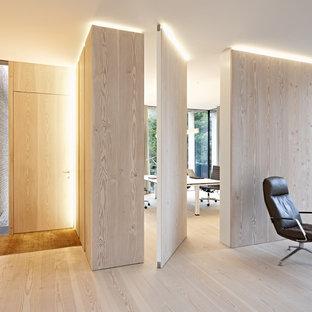 ハンブルクの片開きドアコンテンポラリースタイルのおしゃれな玄関 (淡色無垢フローリング、淡色木目調のドア、ベージュの壁) の写真