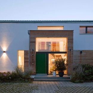 Mittelgroße Moderne Haustür mit brauner Wandfarbe, Betonboden, Einzeltür, grüner Tür und grauem Boden in München