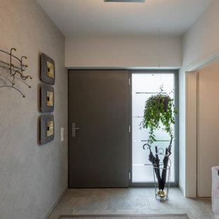 Réalisation d'une petite entrée design avec un couloir, un mur blanc, un sol en carrelage de céramique, une porte noire et un sol gris.