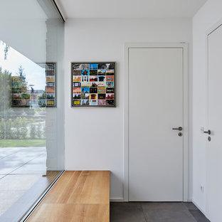Kleiner Country Eingang mit Korridor, weißer Wandfarbe, Einzeltür, weißer Tür und grauem Boden in Köln