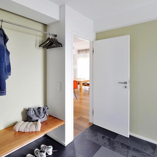 Example of a mid-sized minimalist granite floor and gray floor entryway design in Munich with green walls and a white front door