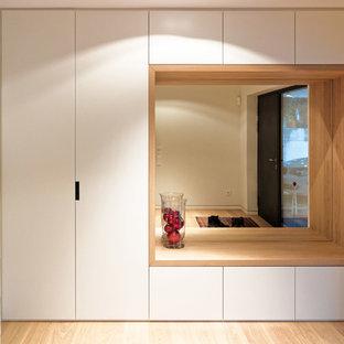 Cette photo montre une très grand entrée tendance avec un mur blanc, un sol en bois clair, un vestiaire et une porte simple.