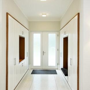 Пример оригинального дизайна: тамбур среднего размера в современном стиле с белыми стенами, двустворчатой входной дверью, стеклянной входной дверью, бетонным полом и белым полом