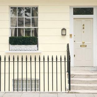 Mittelgroße Klassische Haustür mit gelber Wandfarbe, Einzeltür und Betonboden in Sonstige