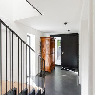 Medium sized contemporary front door in Munich with white walls, vinyl flooring, a single front door, a black front door and grey floors.