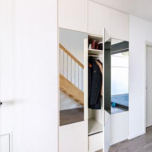 Foto på ett mellanstort funkis kapprum, med vita väggar, laminatgolv, en enkeldörr, en grå dörr och brunt golv