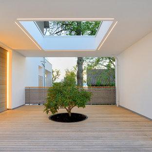 Moderner Eingang mit Foyer, weißer Wandfarbe, braunem Holzboden, Einzeltür und heller Holztür in Sonstige