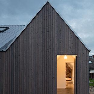 На фото: маленькая входная дверь в скандинавском стиле с белыми стенами, одностворчатой входной дверью, коричневой входной дверью, черным полом и полом из терраццо