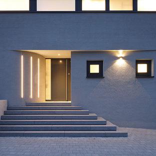 Kleine Moderne Haustür mit grauer Wandfarbe, Einzeltür, schwarzer Tür und grauem Boden