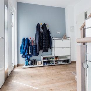 Mittelgroßer Nordischer Eingang mit Stauraum, grauer Wandfarbe, braunem Holzboden, Einzeltür, weißer Tür und braunem Boden in Frankfurt am Main
