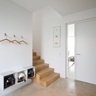 Kleiner Nordischer Eingang mit Foyer, weißer Wandfarbe, Betonboden, Einzeltür, weißer Tür und beigem Boden in München