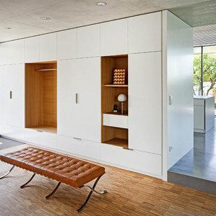 Moderner Eingang mit Foyer, weißer Wandfarbe, braunem Holzboden und braunem Boden in Stuttgart