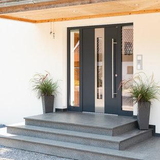 Exempel på en liten modern ingång och ytterdörr, med vita väggar, granitgolv, en enkeldörr, en svart dörr och grått golv