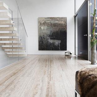 Idées déco pour un très grand hall d'entrée contemporain avec un mur blanc, un sol en travertin, une porte simple et une porte noire.