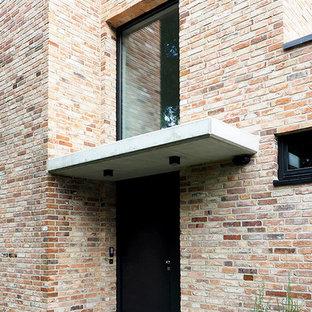 ハンブルクの中くらいの片開きドアコンテンポラリースタイルのおしゃれな玄関ドア (コンクリートの床、黒いドア、レンガ壁) の写真
