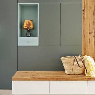 Cette photo montre une entrée scandinave avec un vestiaire, un mur gris et un sol en bois clair.
