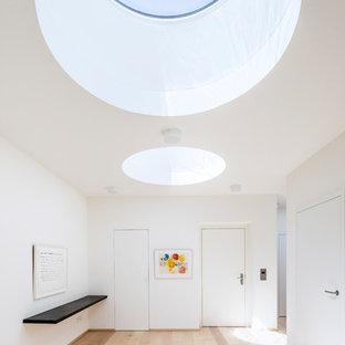 Mittelgroßer Moderner Eingang mit Foyer, weißer Wandfarbe, hellem Holzboden, Einzeltür, weißer Tür und beigem Boden in Köln
