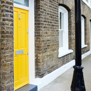 Inspiration for a medium sized scandi front door in London with multi-coloured walls, concrete flooring, a single front door, a yellow front door and grey floors.