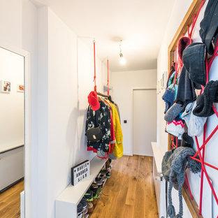 Idéer för en liten eklektisk hall, med vita väggar, mellanmörkt trägolv, en enkeldörr, en vit dörr och brunt golv