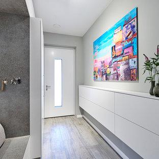 Bild på en mellanstor funkis entré, med grå väggar, laminatgolv och brunt golv