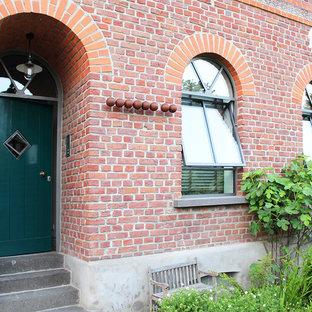 Новые идеи обустройства дома: маленькая входная дверь в стиле кантри с красными стенами, бетонным полом, одностворчатой входной дверью, зеленой входной дверью и серым полом