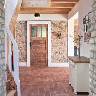 На фото: большое фойе в стиле рустика с одностворчатой входной дверью, входной дверью из темного дерева и красным полом