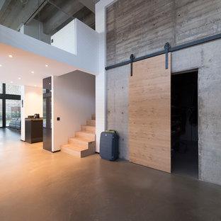 Bild på en stor industriell foajé, med vita väggar, betonggolv och grått golv