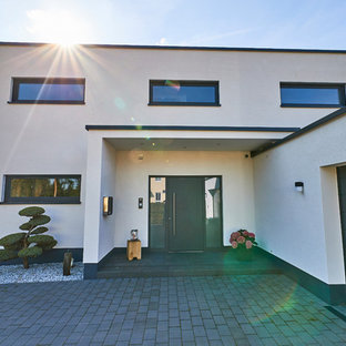 Inspiration for a huge granite floor and black floor entryway remodel in Dortmund with white walls and a white front door