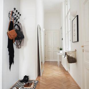 Mittelgroßer Nordischer Eingang mit weißer Wandfarbe, braunem Holzboden und braunem Boden in Hannover
