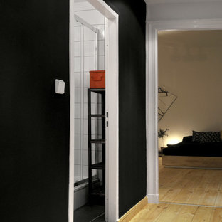 Example of a small trendy light wood floor and brown floor entryway design in Berlin with black walls and a white front door
