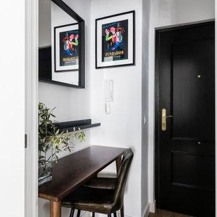 Foto de hall actual, pequeño, con paredes blancas, suelo de madera en tonos medios, puerta simple, puerta negra y suelo marrón
