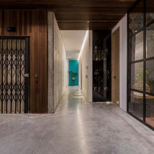 Inspiration pour une grand entrée design avec un couloir, un mur marron, béton au sol, une porte coulissante, une porte noire et un sol gris.